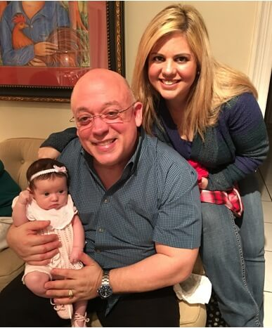 Armando Paz Jr., Jackie Paz, and their infant daughter smiling