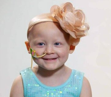 A small girl (approximately 5 years old) with cancer and a tube running down her nose. She is smiling.